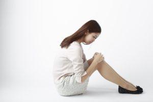 膝の黒ずみを見る女性