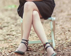 膝を交差させる女性